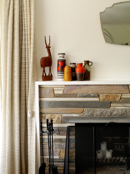 A teak gazelle and a collection of West German pottery sit on the mantle, above the original slate fireplace