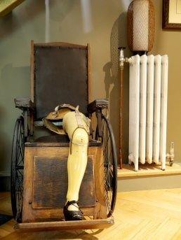 A vintage prosthetic leg from the United Kingdom sits on top the1920s wheelchair